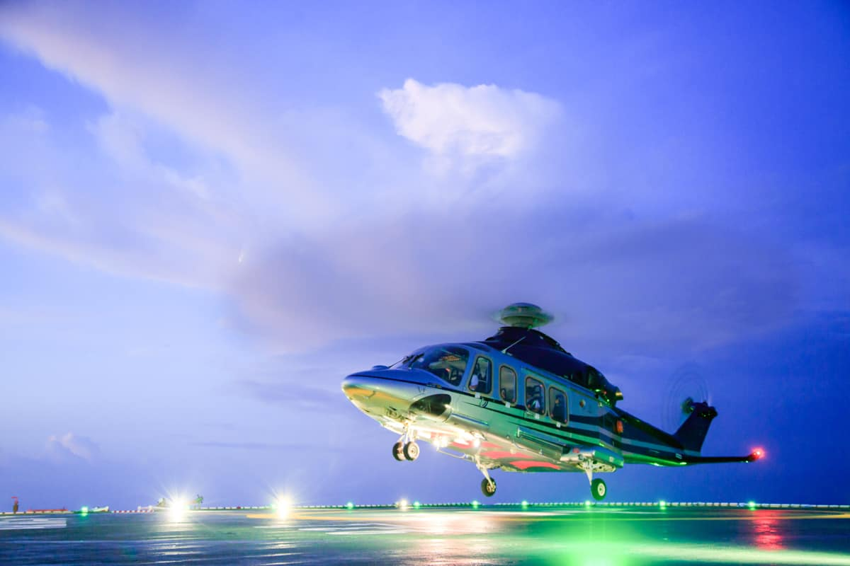 A helicopter lands on an oil rig platform bringing a Emergency Management & Crisis Contingency Services specialist