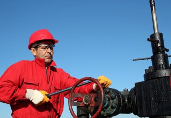Worker in action at pump jack oil well.
